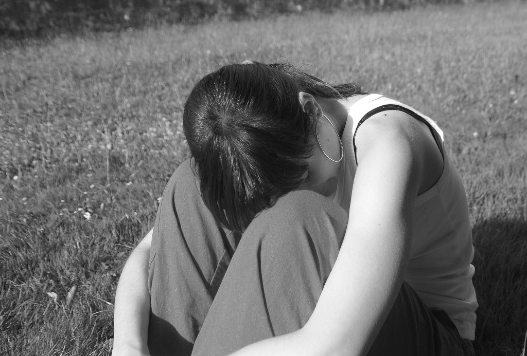 The lonely broken girl sitting in the field