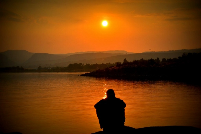 Boy in the evening in front of river and sun