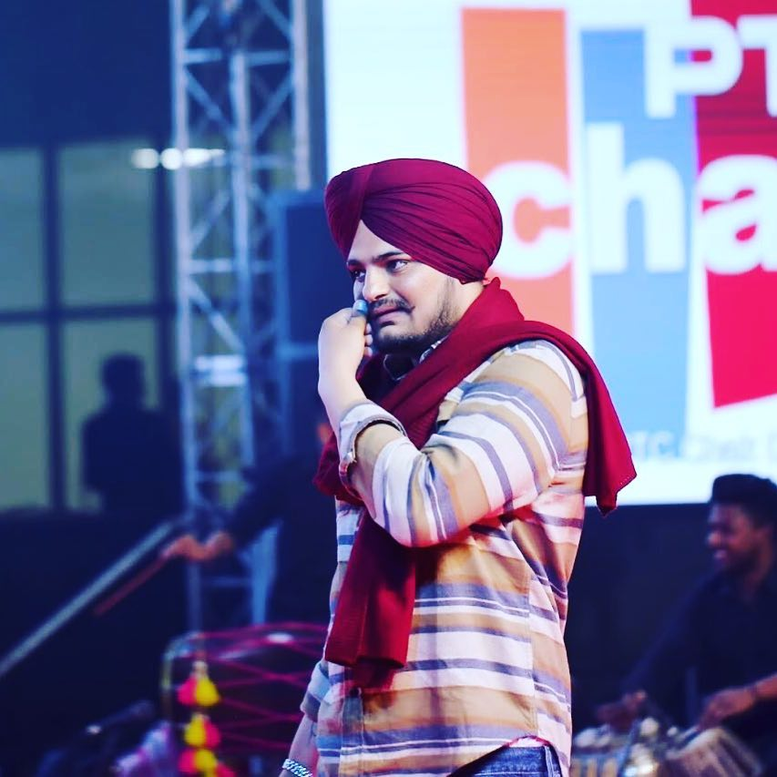 sidhu moose wala is on the stage. he wear shirt and jeans. also he have a red colth on his body. he tie a red turban
