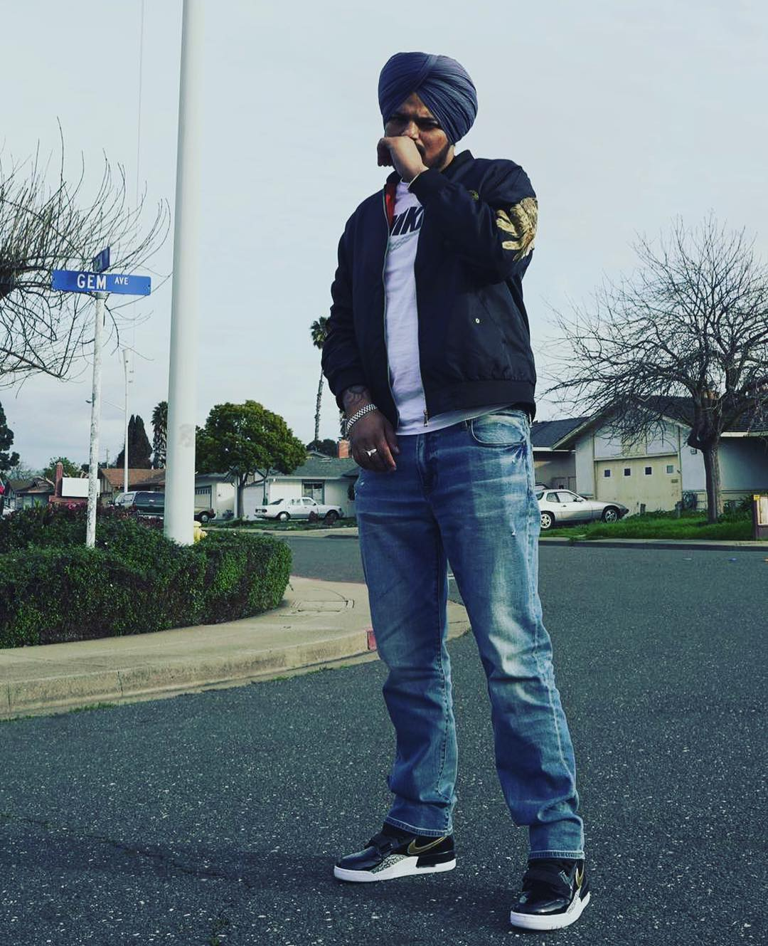 sidhu moose wala standing middle on the road. house ande cars are in the background. he wear white t shirt, blue jacket , blue jeans and black & white shoes. also he tie a blue turan,.