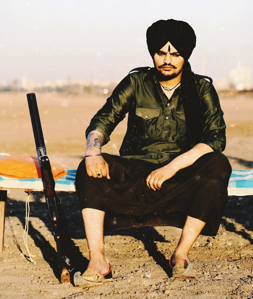 sidhu moose wala sit on manja. gun is lay down near round hom. he wear black kurta chadra. also he tie black turban.