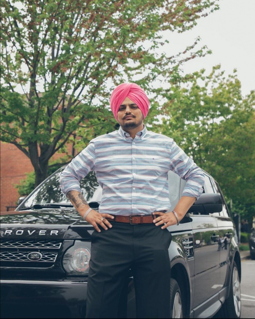 sidhu moose wala standing with black range rover car. he wear shirt with black formal pent. he tie pink turban.