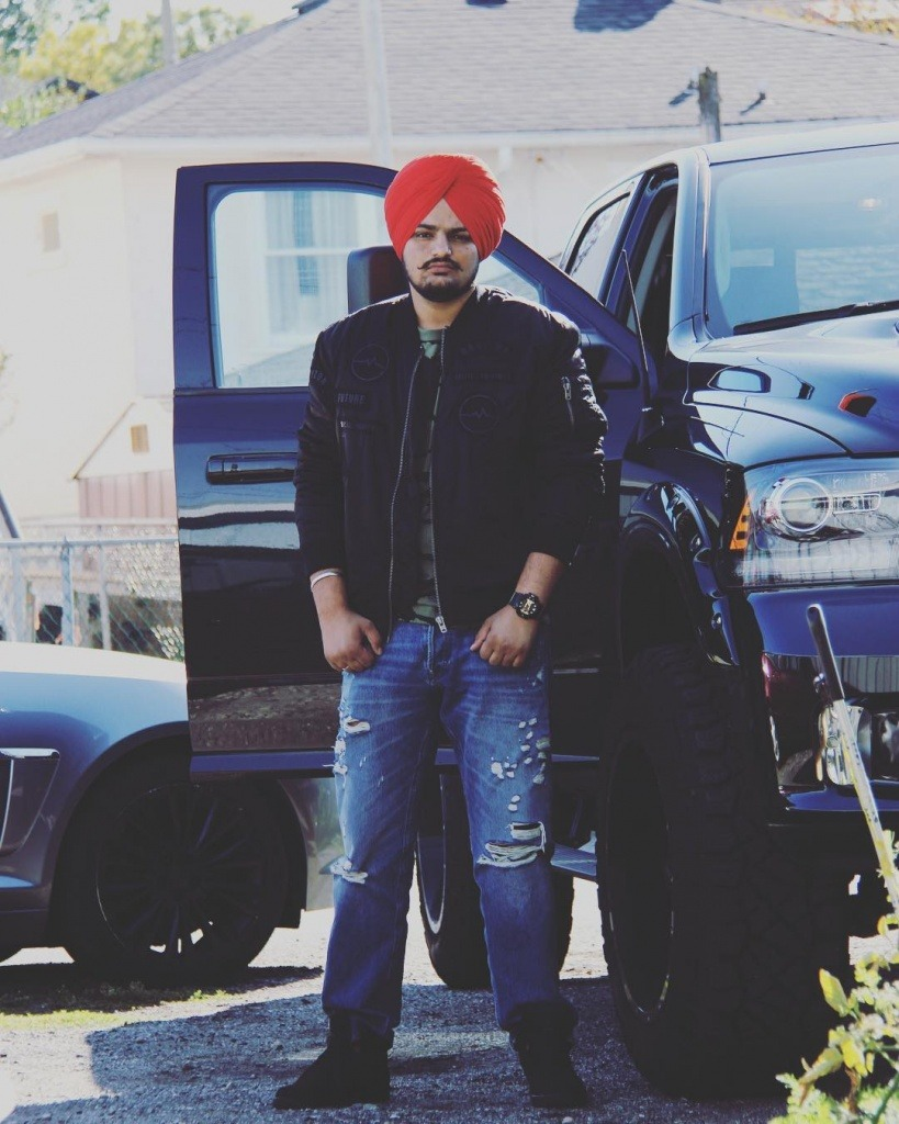 sidhu moose wala is standing with a black car. he wear black jacket and jeans with black shoes. he tie red turban.