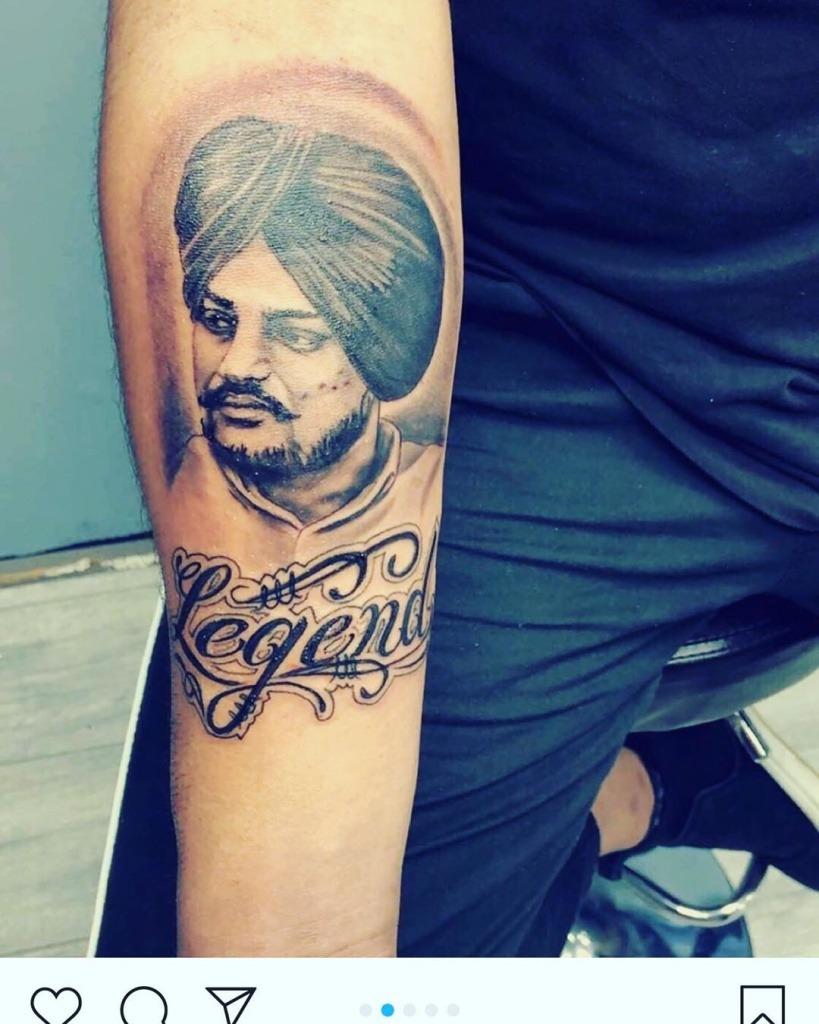 sidhu moose wala tattoo is on someone's arm.  legends is wirte down the tattoo.