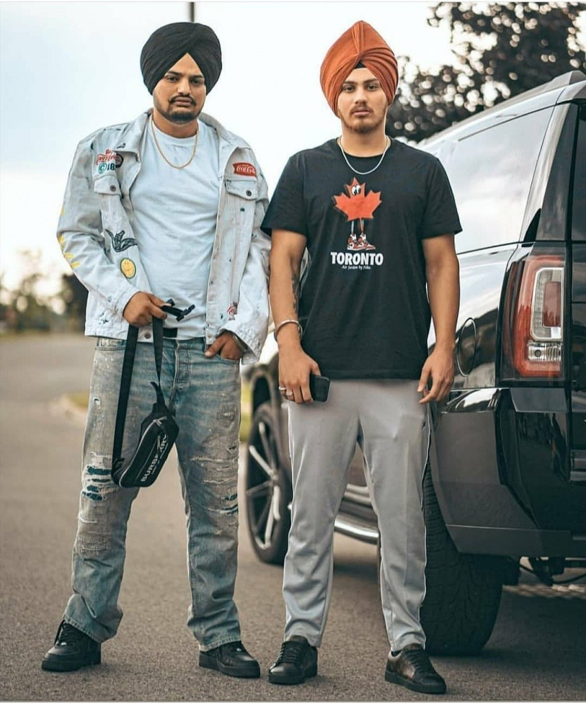 sidhu moose wala is standing with his friend. both are near the black car.sidhu moose wala wear jacket, white shirt and jeans with black shoes. also he tie a black turban. his friend wear black t shirt and gray pent with black shoes. also he tie lite brown turban.
