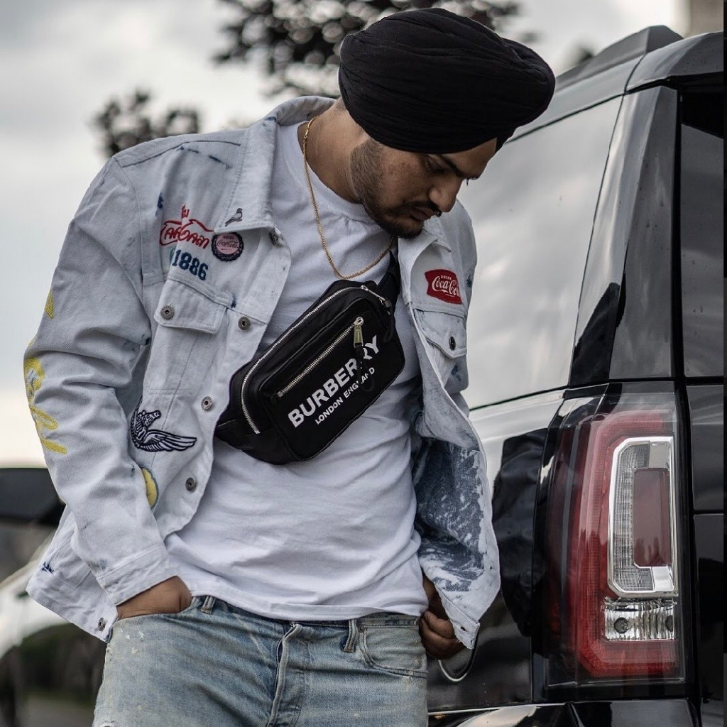 sidhu moose wala standing with black car. he wear white shirt and lite blue jeans & jeans jacket. also he have a bag on his shoulder.
