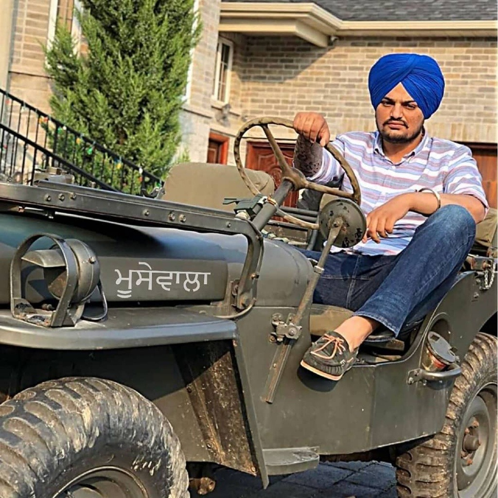 sidhu moose wala sit in jeep. jeep is standing otside the house. sidhu wear shirt and jeans pent with brown shoes. also he tie a blue turban.