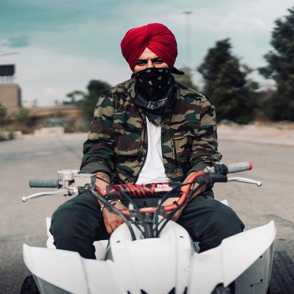 sidhu moose wala is sit on a white vehicle. he hide his face with handkerchief. he wear white t shirt and army colour jacket.