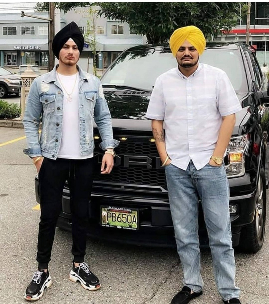 sidhu moose wala and his friend is standing the ford's black car. sidhu wear white shirt and jeans pent. also he tie a yellow turban. his friend wear white t shirt and jeans jacket with black pent.