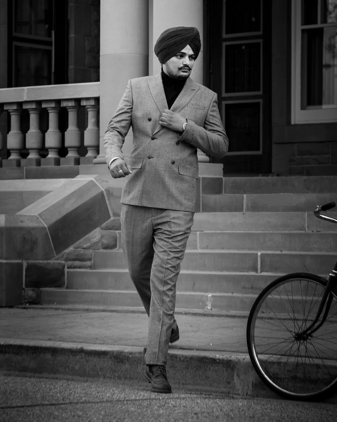 sidhu mooose wala in black and white image. he is coming down from stairs. he wear pent coat and tie a black turan.