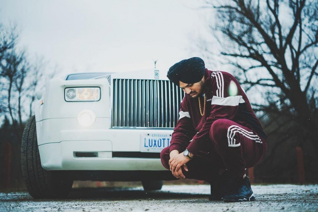 sidhu moose wala sit front of royal white royce . he wear red sports colthes with black shoes. also he wear black turan.