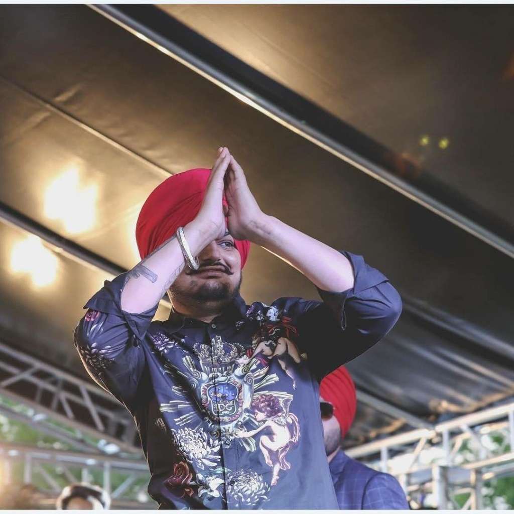 sidhu moose wala is on stage.he is say hello to his fans. he wear blue shirt and tie a red turan.