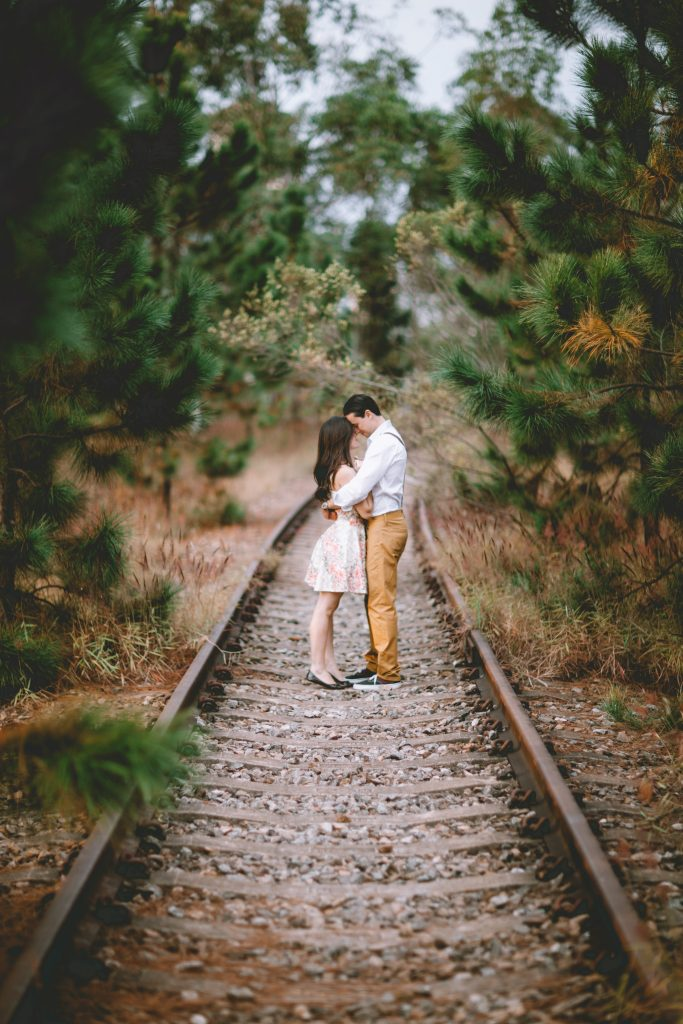 boy and his girlfriend standing between the train track