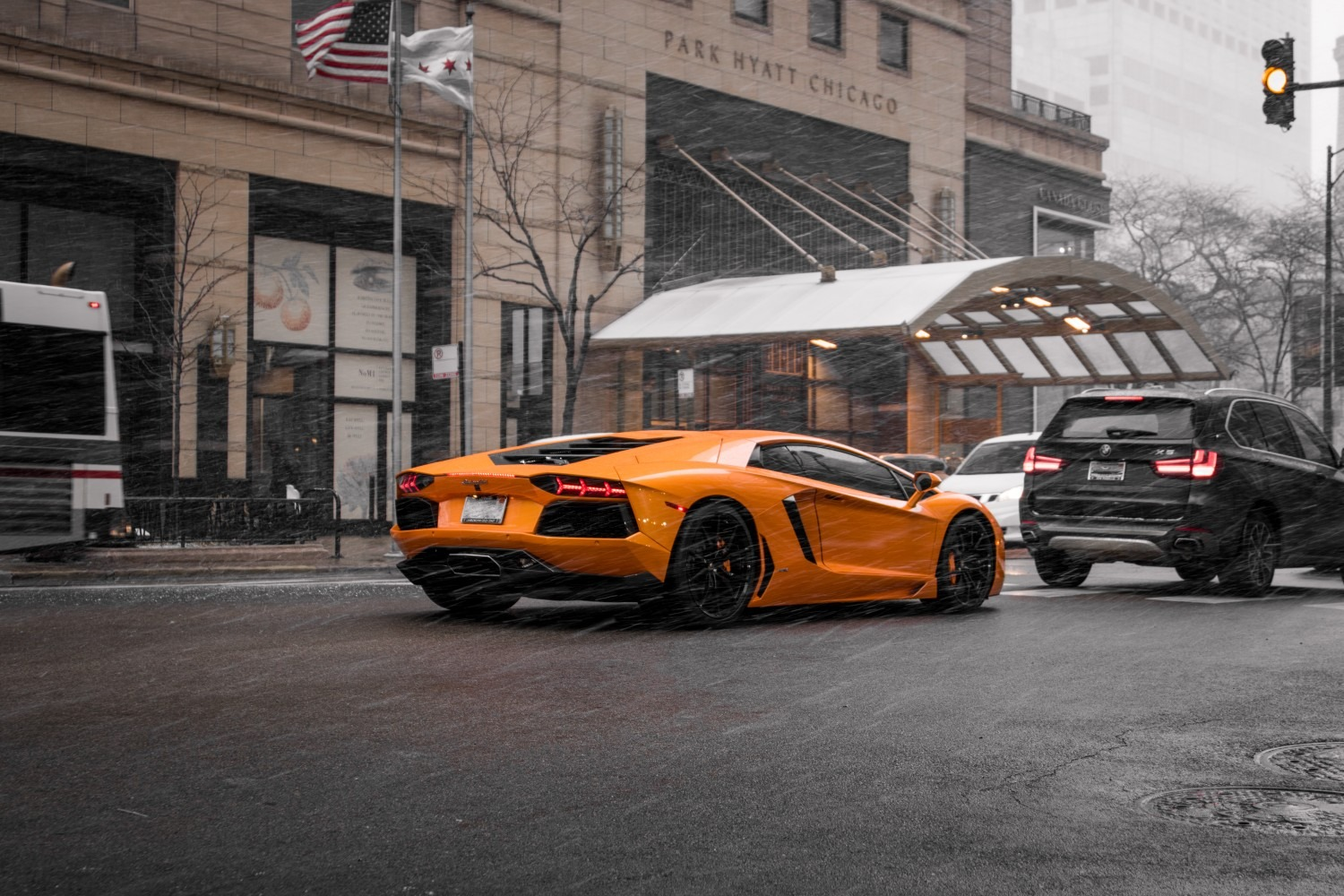 yellow lamborghini aventador car is going  on road. black  car is going front of lamborghini. two flags are stand on side road. rain and wind is coming very fast.