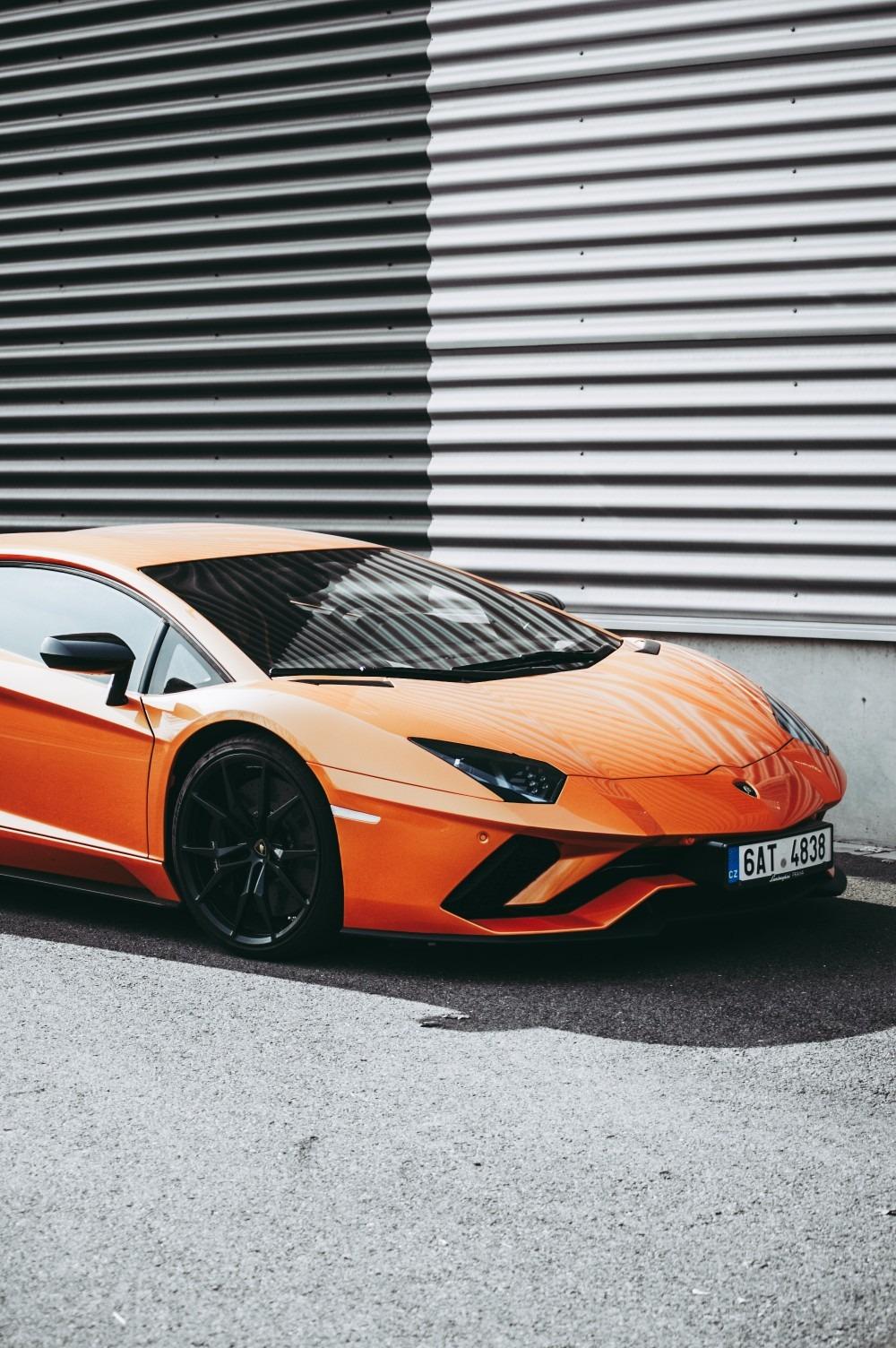 orange Lamborghini Aventador is standing in front of the building.