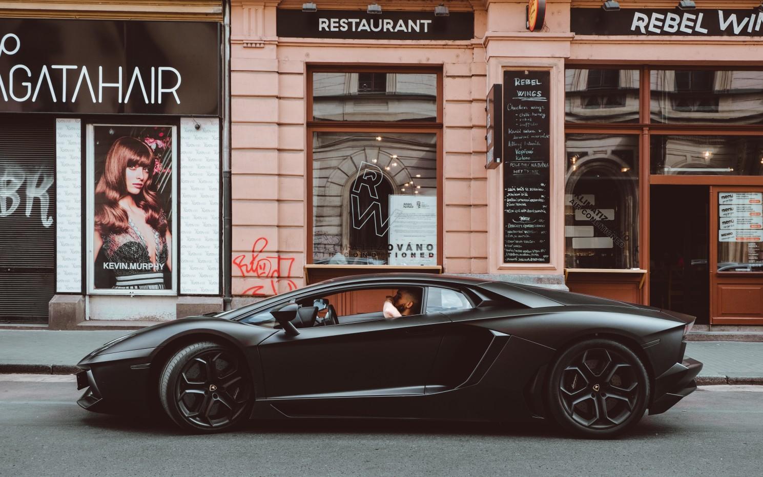 Black Lamborghini Aventador is standing in front of the restaurant.