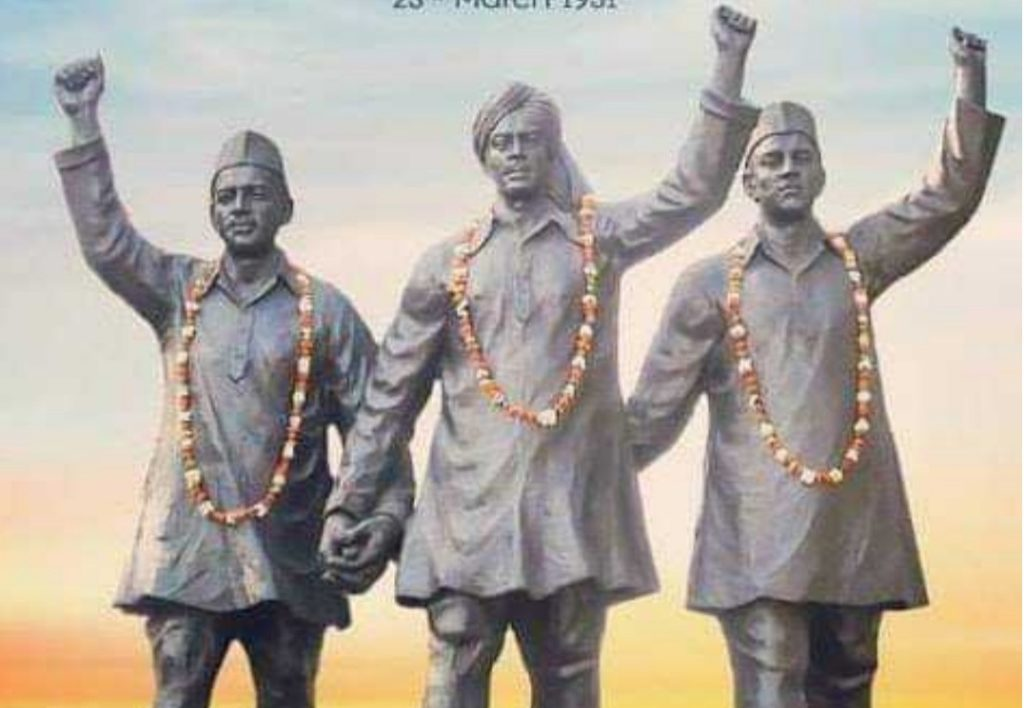 statue of shaheed bhagat singh, rajguru, sukhdev is on front in pic. all have necklace of flowers in their neck.