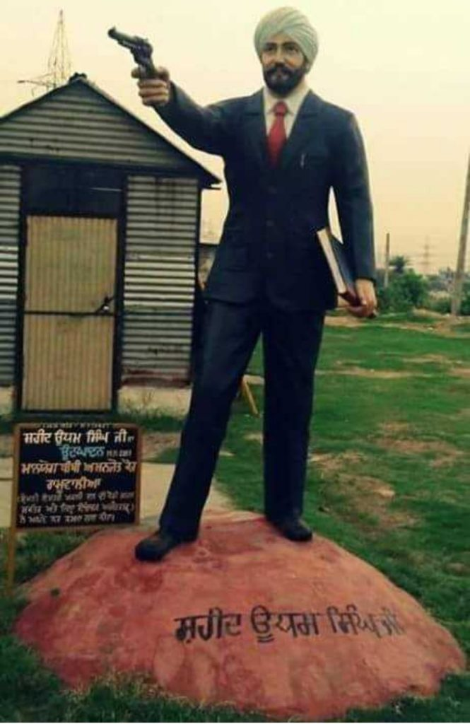 shaheed udham singh is standing on stone in image. udham singh have gun is in his right hand and a book is in his other hand. he tie turban and wear navvy blue pent coat.