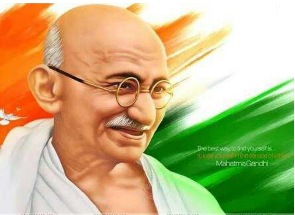 mahatma gandhi ji fornt in image and indian flag is in his back.