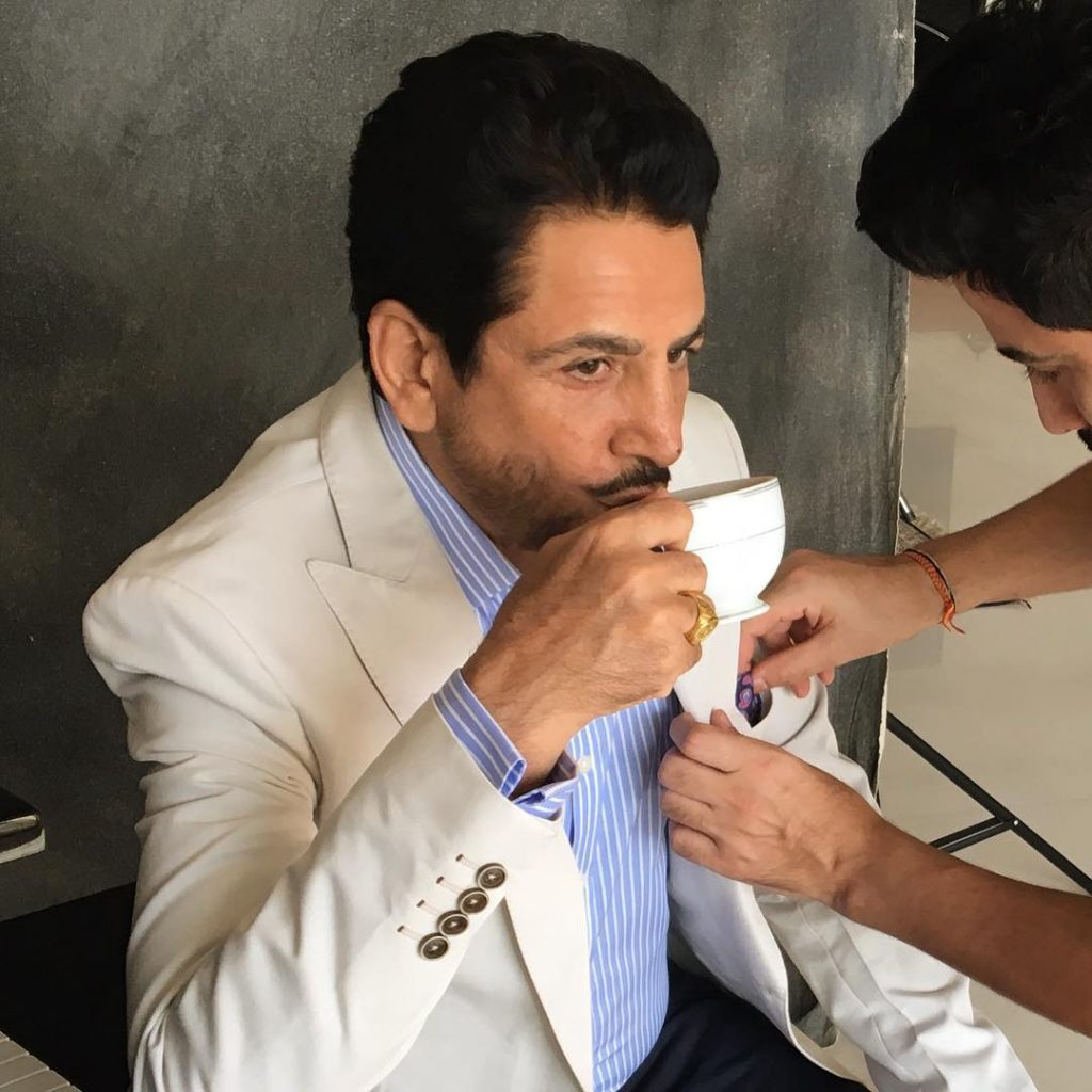 gurdas maan is sit on chair while taking a cup of tea. he wear cream colour coat. and another person is touching his coat.