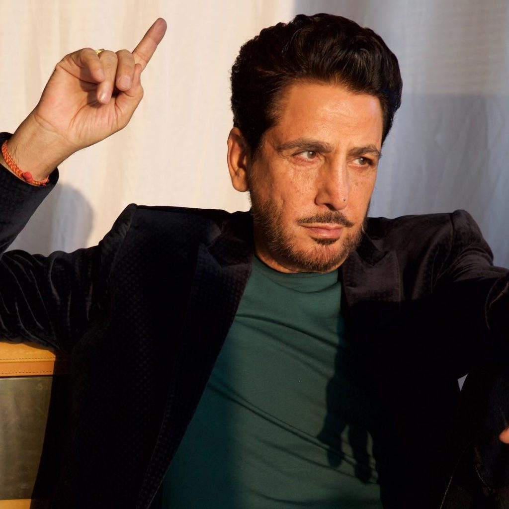 gurdas maan is showing his fingher while sit on sofa. he wear black coat and green t shirt.