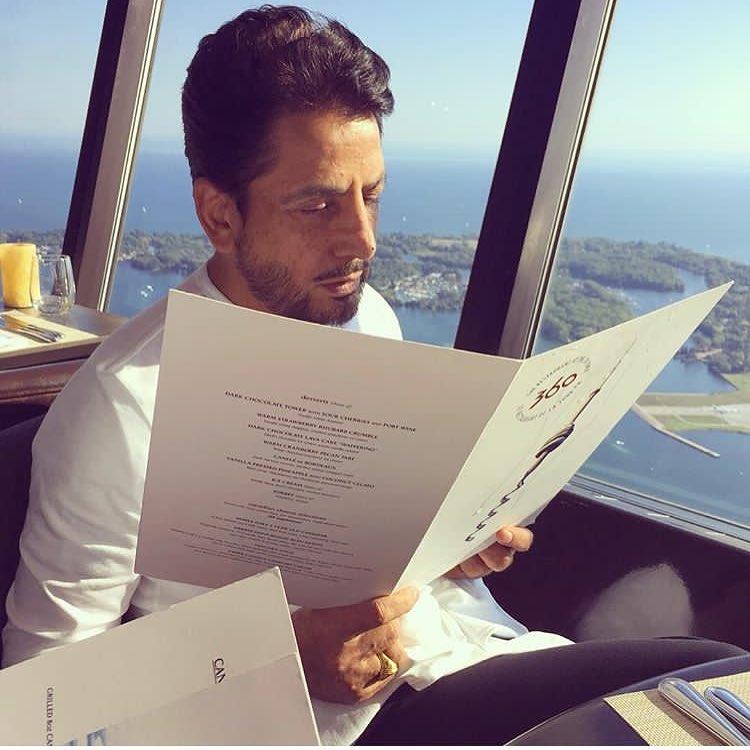 gurdas maan is sit in resturant and reading menu. he have menu card in his hands.