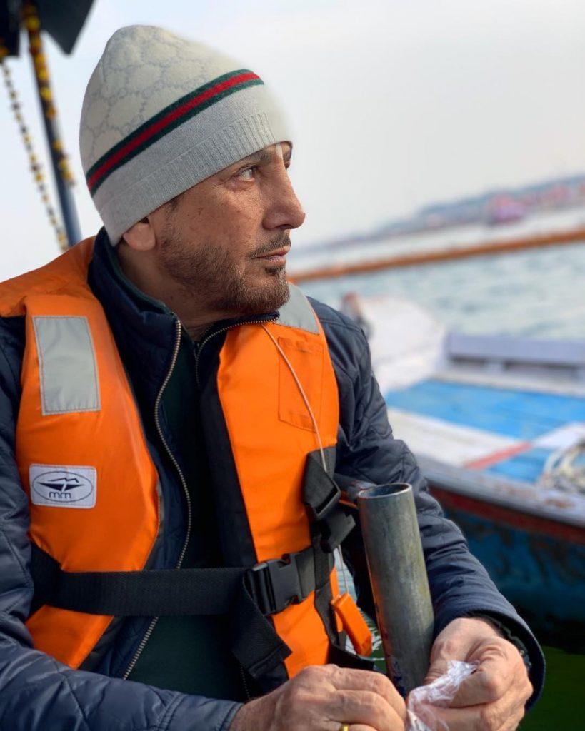 gurdas maan is on boat. he wear safecoat in orange colour.