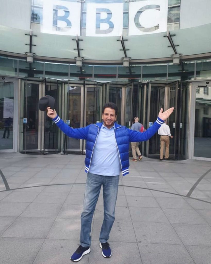 gurdas maan is standing front of bbc. he wear blue coat, sky blue t shirt and jeans.