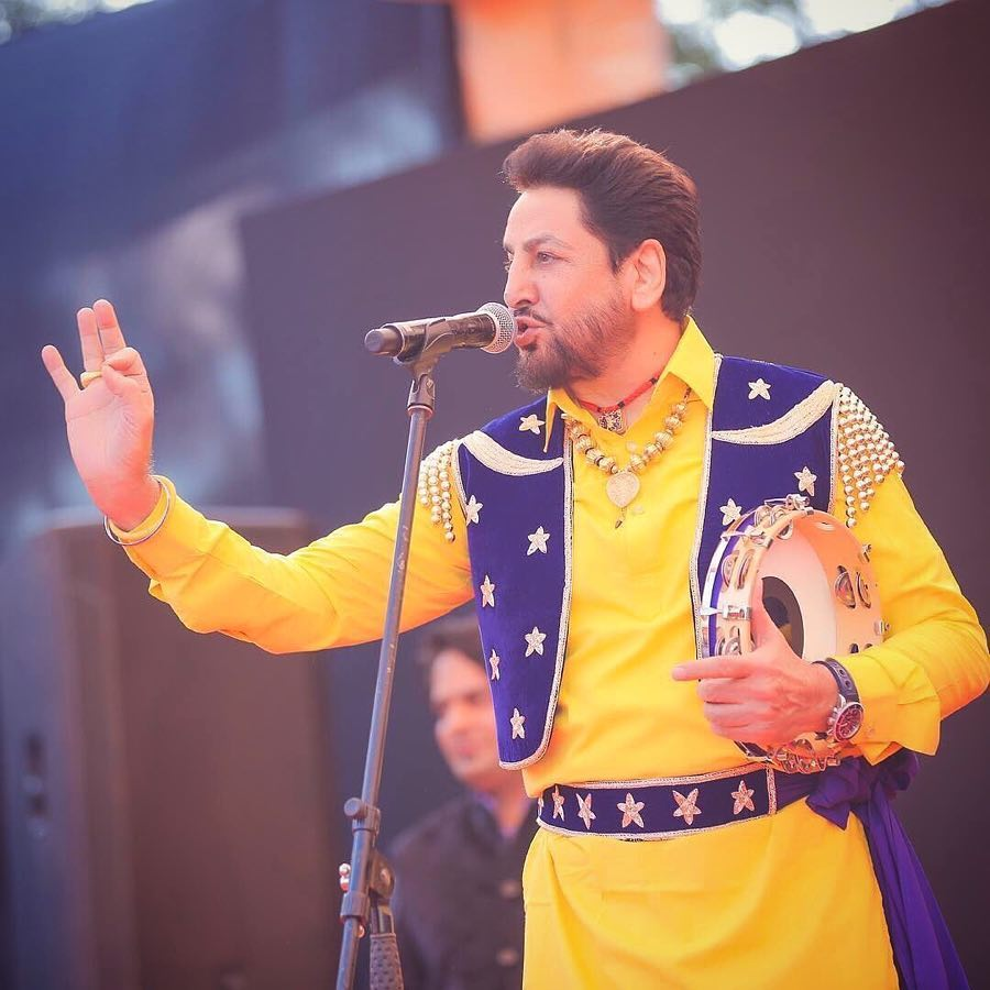 gurdas maan is singing a song on stage. he have a tambourines in his hand. mic stand is front of him.