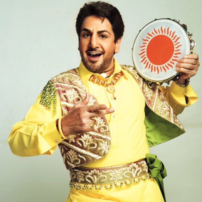 gurdas maan is singing a song. he have tambourines in his left hand.
