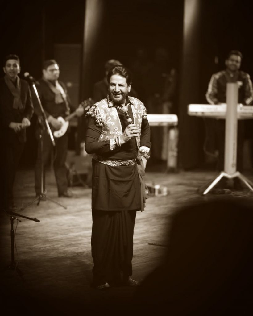 gurdas maan is singing a song on stage. he have a mic in his hand. other singer and muiscan are in background.