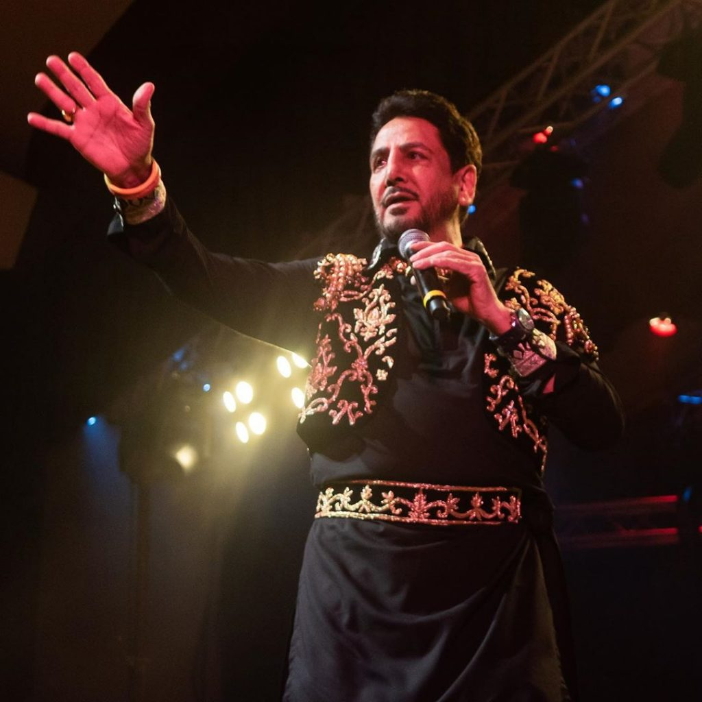 gurdas maan have mic in his hand. he is singing a song on stage.
