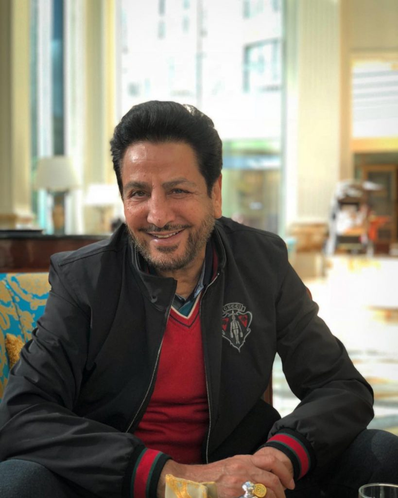 gurdas maan sit on the sofa. he wear jacket red t shirt and a golden ring in his hand.