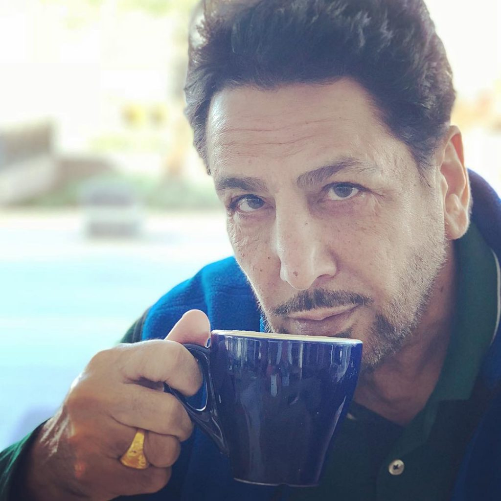 gurdas maan is taking a cup of tea. cup is in blue colour. he wear green t shirt and blue jacket.