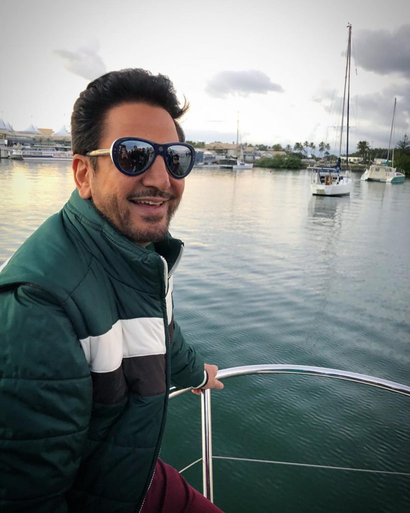 gurdas maan is in a leak on boat. he have sunglasses and green jacket.