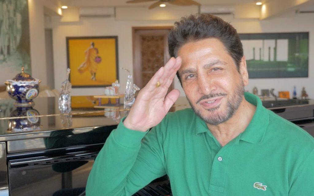 gurdas maan is saluteing in image. he sit in a room. he wear green t shirt.