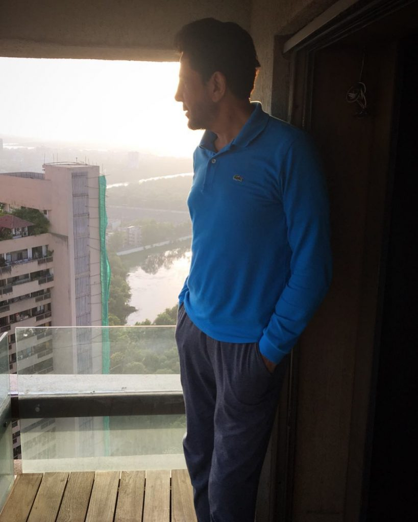 gurdas maan standing to high in balcony. he is looking other bulidings. he wear blue t shirt and gray pent.