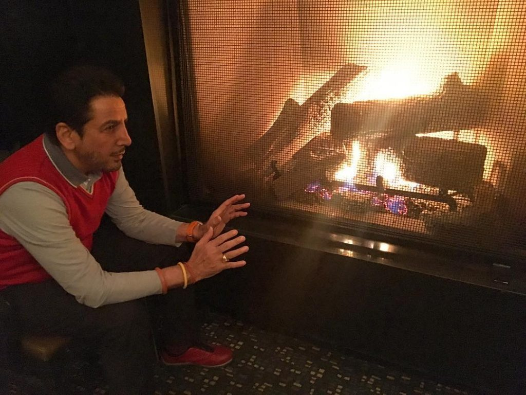 gurdas maan is sit near the fire. he wear gray t shirt and red hoodie. also he wear black pent and red shoes.