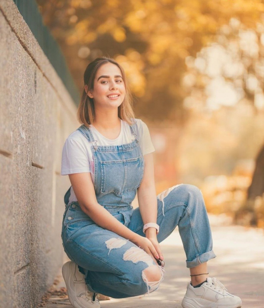sunanda sharma sit the short wall. she sit one side the road. she wear white t shirt and shhoes. also she wear lite blue jeans.