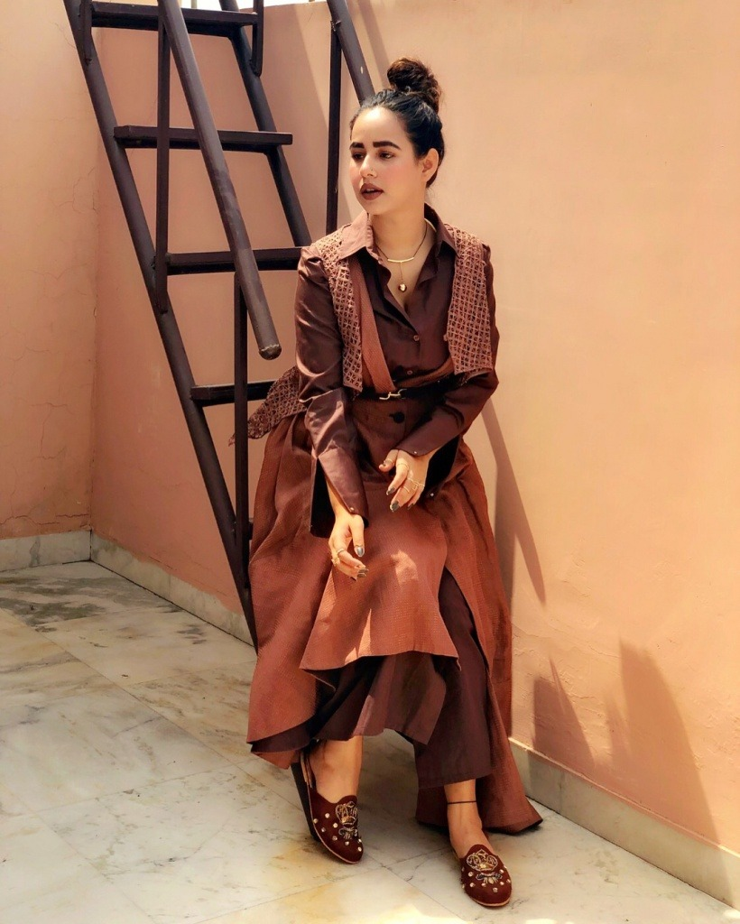 sunanda sharma is sit on the stairs. she wear drak and lite brown colour dress.