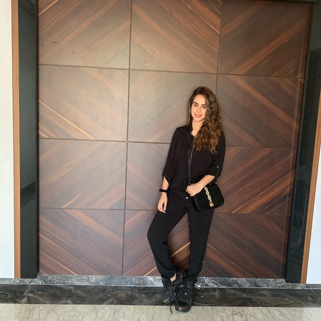 sunanda sharma is standing with wood wall. she is in black dress. also he have black bag.