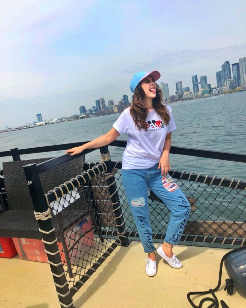 sunanda sharma is on the boat. city is comes in background. she wear white t shirt and white shoes. also she wear lite blue jeans.
