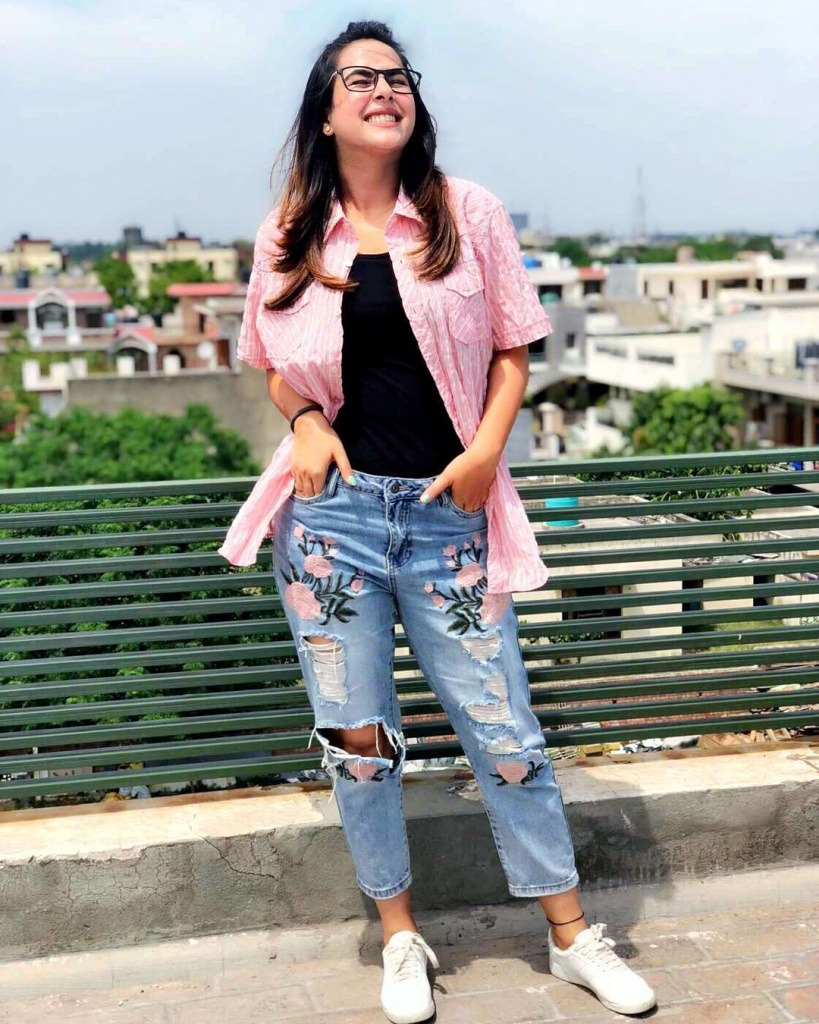 sunanda sharma is standing on high place. whole city comes in back ground. she wear pink shirt, black t shirt and jeans.