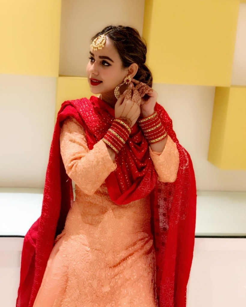 sunanda sharma is standing with white and yellow wall. she wear cream and red colour punjai suit.