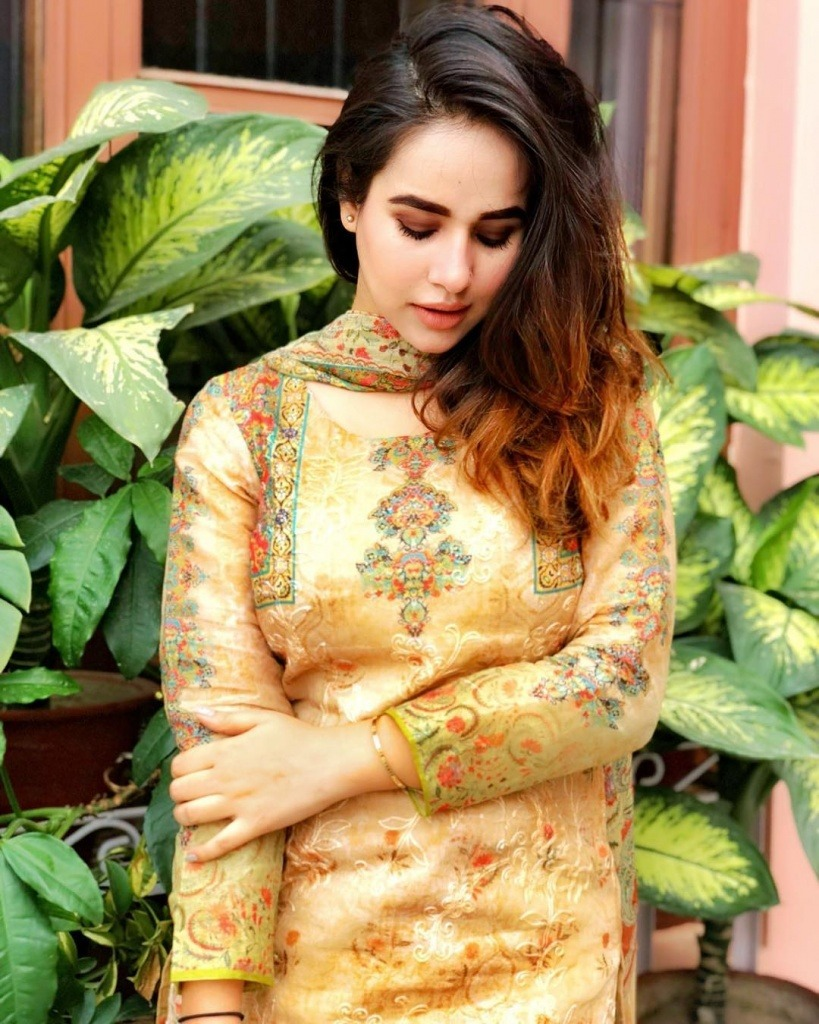 sunanda sharma standing outside the house. she wear a punjabi suit in golden colour.