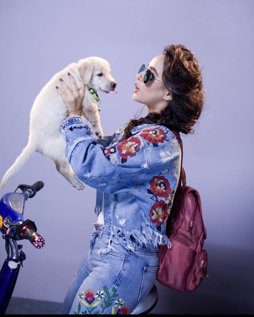 sunanda sharma have a puppy in her hands. she sit on the bicycle. also she have a purple ag on her back.